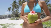 sedento : Happy tourist bikini woman drinking fresh coconut water on Caribbean beach in Barbados vacation. Closeup of unrecognizable woman holding healthy tropical fruit snack during summer holidays.