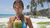 sağlıklı : Cute Asian girl on beach vacation drinking fresh coconut water from a green young coconut fruit cut from a palm tree. Healthy lifestyle woman eating local food on Caribbean travel holiday.