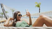 lying : Beach woman taking smartphone selfie picture relaxing on holiday. Young casual cute girl lying down in outdoor swing hammock bed enjoying tropical vacation sunbathing under the sun using mobile phone.