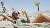 patio : Happy beach woman reading sms texting on smartphone lying on hammock relaxing on tropical vacation. Young casual cute girl lying down in outdoor swing bed enjoying sun sunbathing using mobile phone. Stock Footage