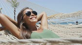 plaża : Summer vacation woman lying down on beach hammock putting on sunglasses relaxing sunbathing under the tropical sun resting on outdoor patio furniture swing bed at Caribbean resort. Wideo