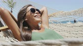 мода : Happy beach vacation woman putting on aviator sunglasses relaxing lying down on outdoor patio hammock tanning smiling happy sunbathing during summer holidays. Asian woman on tropical vacations.