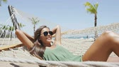 patio : Summer vacation woman lying down on beach hammock putting on sunglasses relaxing sunbathing under the tropical sun resting on outdoor patio furniture swing bed at Caribbean resort. Asian young adult. Stock Footage