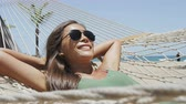солнечный : Happy beach girl tanning in aviator sunglasses lying down relaxing in outdoor bed hammock smiling happy sunbathing during summer holidays. Asian woman on tropical destination getaway. Стоковые видеозаписи