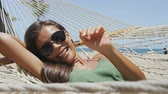 holky : Happy beach girl tanning in aviator sunglasses relaxing in outdoor bed hammock saying hi waving hello at camera smiling happy during summer holidays. Asian woman on tropical destination getaway.