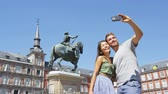 pessoas : Tourists couple taking selfie using smart phone in Madrid Spain on Plaza Mayor. Happy people taking photos. Young woman and man on famous square in front of statue of Felipe 3rd