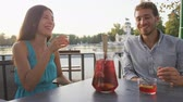 vinho tinto : Couple drinking sangria toasting happy having fun sitting at cafe table outdoors in Madrid, Spain in El Retiro city park. Romantic couple lifestyle in Buen Retiro Park, Parque el Retiro. SLOW MOTION.