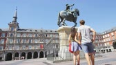 pomalý : Tourists in Madrid Spain on Plaza Mayor walking holding hands. Cheerful excited couple, young woman and man on famous square in front of statue. Spain