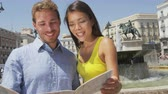 espanhol : Tourists couple with map in Madrid. Sightseeing people looking at map for tourist destination attraction and famous landmarks while visiting Puerta del Sol in Madrid, Spain. Multiracial couple.
