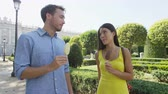 конфеты : Romantic couple eating ice cream at park. Woman and man eating ice cream bar on stick happy walking outdoor in summer. Madrid, Spain