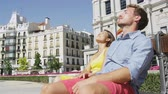 sentar se : Couple relaxing on bench enjoying sun with eyes closed in city square in Madrid, Plaza de Oriente, Famous landmark in Madrid, Spain. Woman and man tourist taking break from sightseeing
