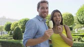creme : Romantic couple eating ice cream at park. Woman and man eating ice cream bar on stick biting looking happy at camera outdoor in summer