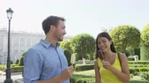 конфеты : Romantic couple eating ice cream at park. Woman and man eating ice cream bar on stick laughing happy on date talking outdoor in summer. Madrid, Spain