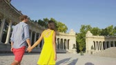 rei : People walking in Madrid in El Retiro park. Couple holding hands on romantic walk by Madrid tourist attraction, the Monument to King Alfonso XII of Spain, Monumento a Alfonso XII