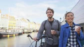 крейсерский : Copenhagen couple. People walking in Nyhavn, old port. Famous tourist attraction destination in Denmark Young multiracial happy couple with bicycle bike and coffee.