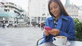 мобильный : Asian business woman texting or reading news on smart phone drinking coffee at outdoor terrace cafe. Stroget, Copenhagen, Denmark, Europe. SLOW MOTION