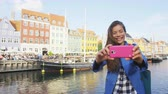 mixed race : Asian tourist woman taking selfie at Copenhagen Nyhavn. Famous landmark, northern Europe destination, the old town waterfront water canal in the capital Kobenhavn in Denmark, Scandinavia.
