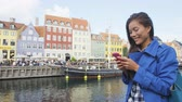 mixed race : Woman on phone app at Copenhagen Nyhavn Denmark. Famous landmark, northern Europe destination, the old town waterfront water canal in the capital Kobenhavn in Denmark, Scandinavia. Stock Footage