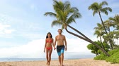 caminhada : Hawaii beach couple walking on hawaiian beach, Kaanapali beach, Maui, Hawaii, USA. Travel vacation Asian, Caucasian couple relaxing on famous hawaiian beach destination for summer travel holidays. Stock Footage