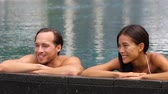 luxuoso : Honeymoon couple relaxing together in an infinity swimming pool in luxury resort spa retreat beach destination. Luxurious hotel travel vacation. People relaxed enjoying summer holidays. 59.94 FPS.