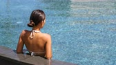 生活方式 : Swimming pool spa retreat relaxation. Relaxing woman lying from the back on infinity edge enjoying sun and serenity in summer holiday travel vacation at resort hotel. Unrecognizable people holidays.