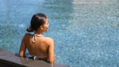 спа : Travel luxury wellness resort bikini woman relaxing in swimming pool. Hydrotherapy spa retreat from behind on side of infinity pool looking away at blue water copyspace. Relaxation vacation concept.
