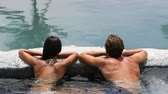 rega : Spa couple happy in wellness hot tub jacuzzi laughing having fun being in love. Happy young lovers on honeymoon vacation travel to luxury resort spa retreat. Handsome man and beautiful asian woman.
