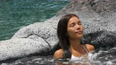 banho : Spa wellness - woman relaxing in hot tub whirlpool jacuzzi outdoor at luxury resort spa retreat. Happy young mixed race Asian Caucasian female model relaxed resting in water near pool on vacation.