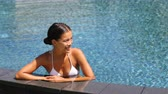 bem aventurança : Happy woman enjoying swimming pool vacation at tropical resort hotel. Asian chinese bikini girl on the side of infinity pool edge smiling relaxing in blue water on sunny summer day vacation getaway. Vídeos