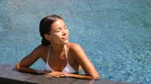 zdraví : Luxury resort woman relaxing in infinity swim pool. Asian young adult lying down in swimming pool of beach resort for summer holidays or travel vacations. 59.94 FPS.