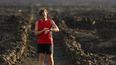 timer : Running man looking at smart watch heart rate monitor smartwatch GPS. Runner stopping running to look at smart watch fitness tracker. Male athlete during trail run.