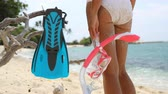 mergulho : Closeup of sexy legs of bikini woman with snorkeling equipment standing looking at ocean. Girl holding blue flippers and mask ready for snorkel. Scuba diving beach vacation concept. 59.94 FPS.