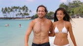 casal : Beautiful sexy suntan people. Happy young interracial couple with slim and fit body relaxing walking on tropical paradise beach during summer vacation holiday. Travel relaxation sun skin care concept.