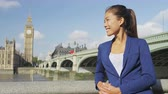 spojené království : Young urban professional business woman portrait by Westminster Bridge in London, England. Multicultural Asian Caucasian businesswoman enjoying her success on beautiful day in London.