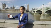 spojené království : Business woman taking selfie using phone in London on business travel. Businesswoman smiling at camera with Thames river, Big Ben and Westminster bridge background. Asian woman using smartphone.