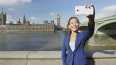 spojené království : Businesswoman taking selfie using phone in London on business travel. Business woman smiling at camera with Thames river, Big Ben and Westminster bridge background. Asian woman using smartphone. Dostupné videozáznamy