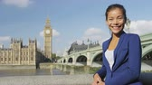 tamisa : Business woman portrait. Businesswoman in London smiling at camera by Westminster Bridge. Mixed race Asian Caucasian young urban professional enjoying her success on sunny day in London. Vídeos