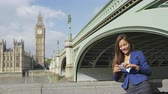 spojené království : Businesswoman on phone using smartphone app on business travel by Westminster Bridge, London, England. Young business woman smiling happy wearing blazer outdoors. Urban female professional, 20s.