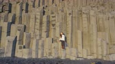 vulcão : Iceland tourist at beach sitting on basalt columns on Reynisfjara beach, the black sand beach of Vik, South Iceland coast. Happy woman visiting tourist attraction destination. RED EPIC SLOW MOTION