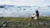 písemný : Iceland nature landscape Jokulsarlon glacial lagoon - ICELAND text written with rocks. Woman enjoying view visiting tourist destination landmark attraction glacier lake, Iconic Vatnajokull. RED EPIC.