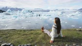 escrita : Iceland tourist enjoying Jokulsarlon glacial lagoon - ICELAND text written with rocks. Woman visiting destination landmark attraction glacier lake, Iconic Vatnajokull nature landscape. RED EPIC.