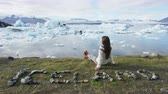 escrita : Iceland nature landscape Jokulsarlon glacial lagoon - ICELAND text written with rocks. Woman enjoying view visiting tourist destination landmark attraction glacier lake, Iconic Vatnajokull. RED EPIC.