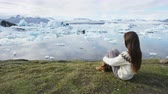 písemný : Iceland tourist enjoying Jokulsarlon glacial lagoon - ICELAND text written with rocks. Woman visiting destination landmark attraction glacier lake, Iconic Vatnajokull nature landscape. RED EPIC.