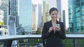 業務 : Woman sms texting using app on smart phone in city business district. Young business woman using smartphone smiling happy wearing suit jacket outdoors. Urban female professional in her 20s.