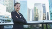 brasão : Business woman portrait of young female urban professional businesswoman in suit standing outside office building with arms crossed. Confident successful multicultural Chinese Asian  Caucasian woman. Stock Footage