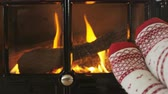 уютный : Feet in warm socks in front of fireplace in winter. Woman wearing socks against fireplace in living room. Female is warming her legs during winter. SLOW MOTION shot Стоковые видеозаписи