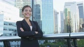 propriedade : Happy business woman portrait of young female urban professional businesswoman in suit standing outside office buildings cross-armed. Confident successful multicultural Chinese Asian  Caucasian woman