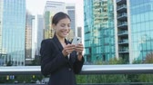 sorridente : Phone. Business woman using phone sms texting using app on smartphone in city business district. Young businesswoman using mobile phone smiling happy in suit jacket outdoors. Urban female professional