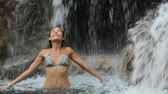 безмятежность : Girl in bikini bating under waterfall in pristine natural pool serene and happy. Woman raising arms up in pure joy and happiness swimming in amazing nature. 59.94 FPS SLOW MOTION.