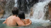 романтический : Happy couple bathing by waterfall in embracing and hugging romantic on honeymoon.